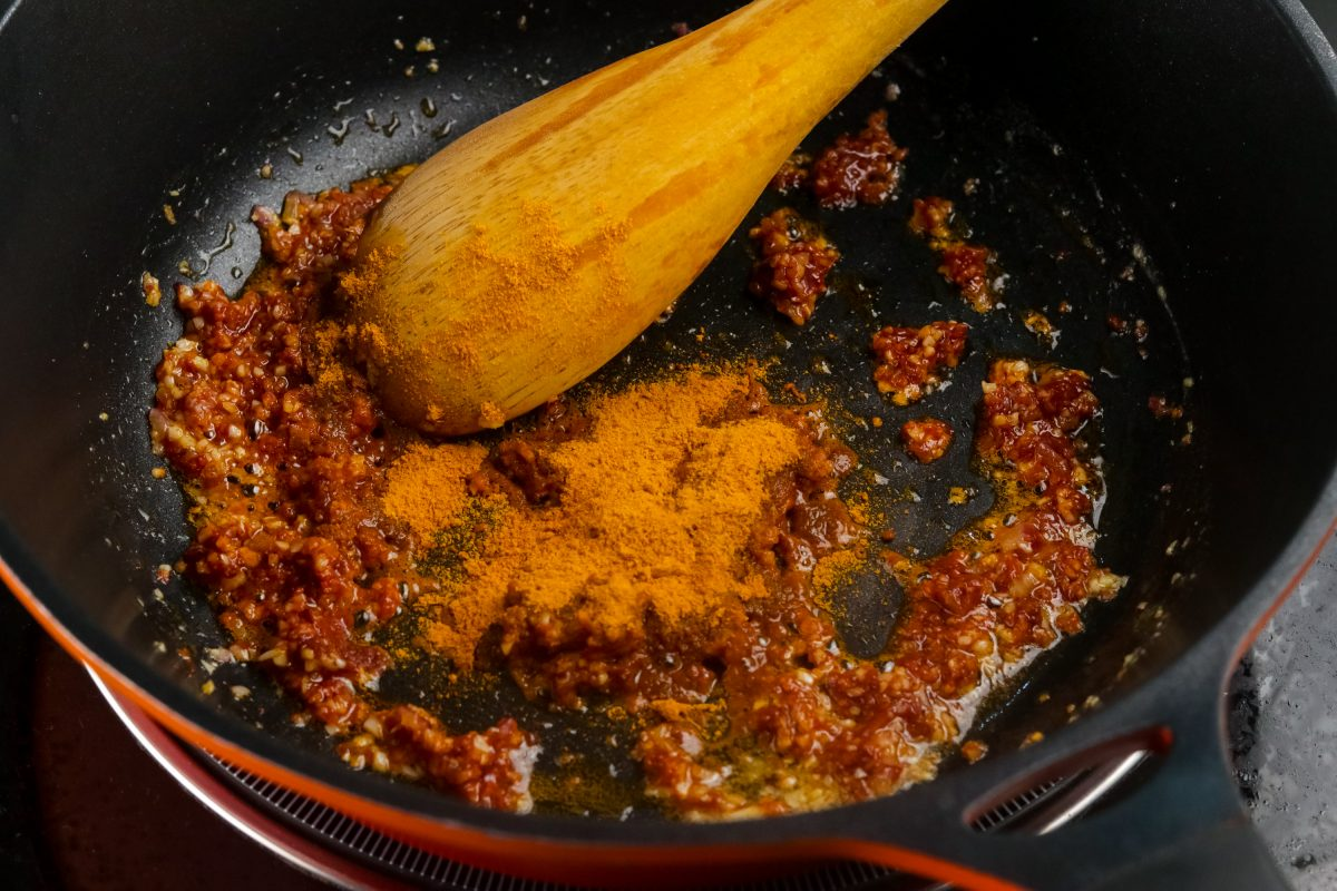 Add tomato paste and curry powder. Roast for about a minute