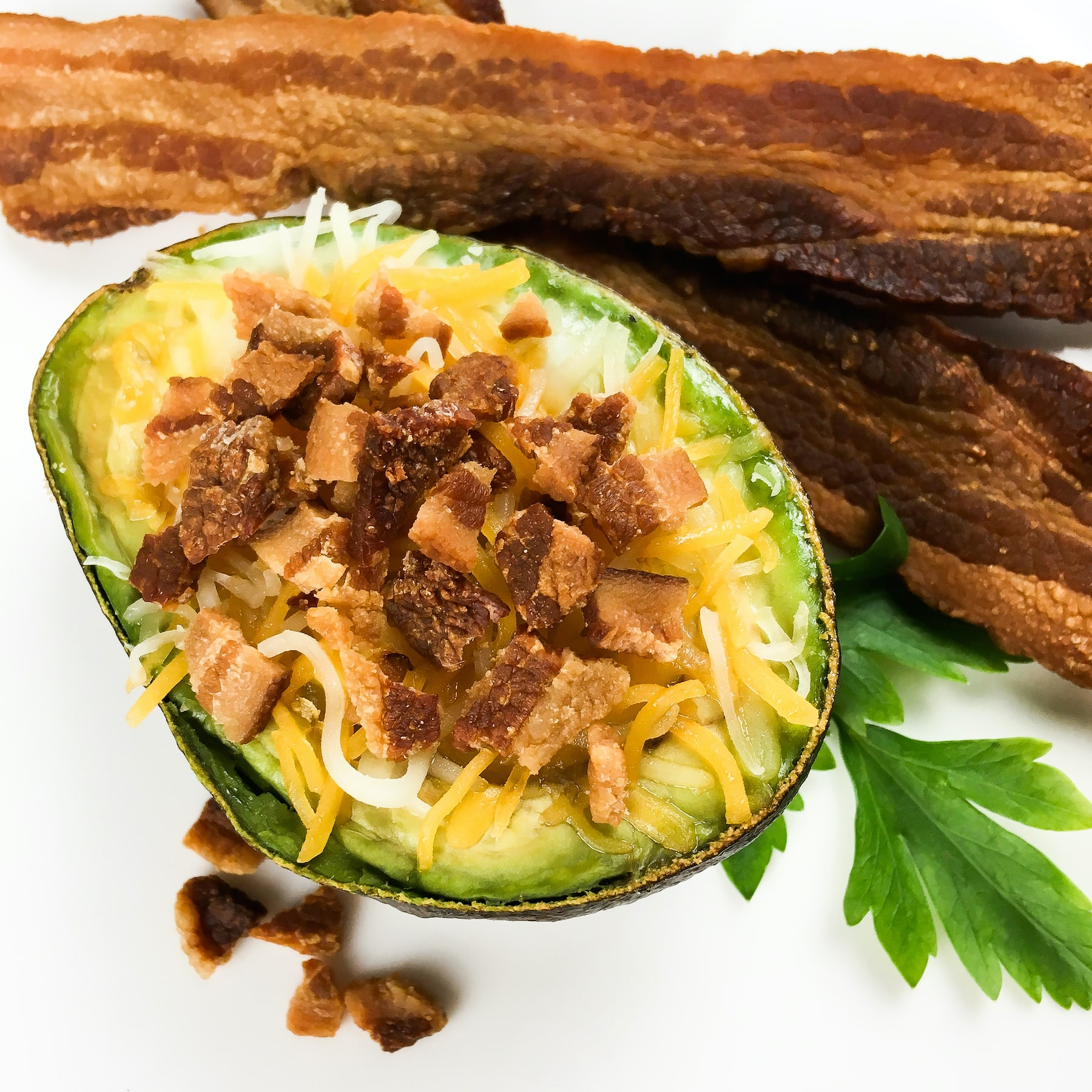 Top each baked avocado half with shredded Cheddar Jack cheese and crispy bacon pieces.